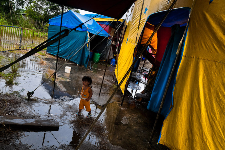 A little Colombian girl walks through puddle at the Circo Anny, a family run circus wandering the Amazon region of Ecuador,