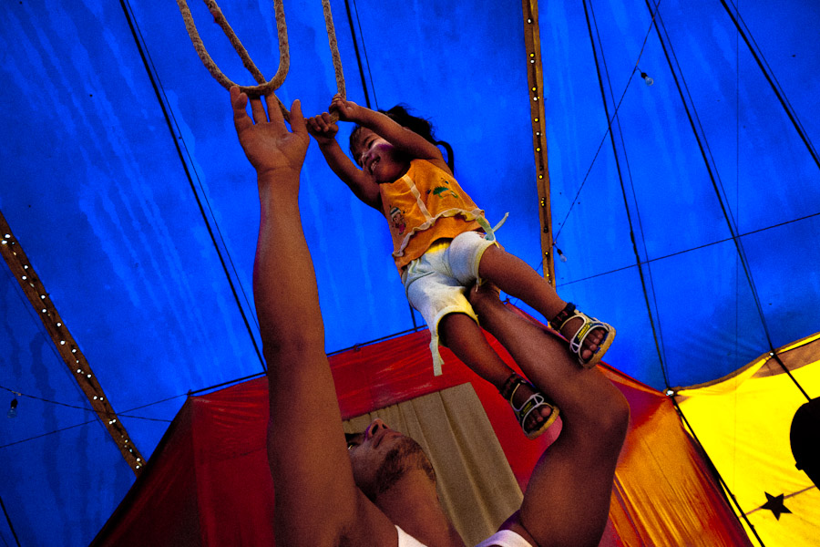 A little Colombian girl does a trapeze training with help of his father.