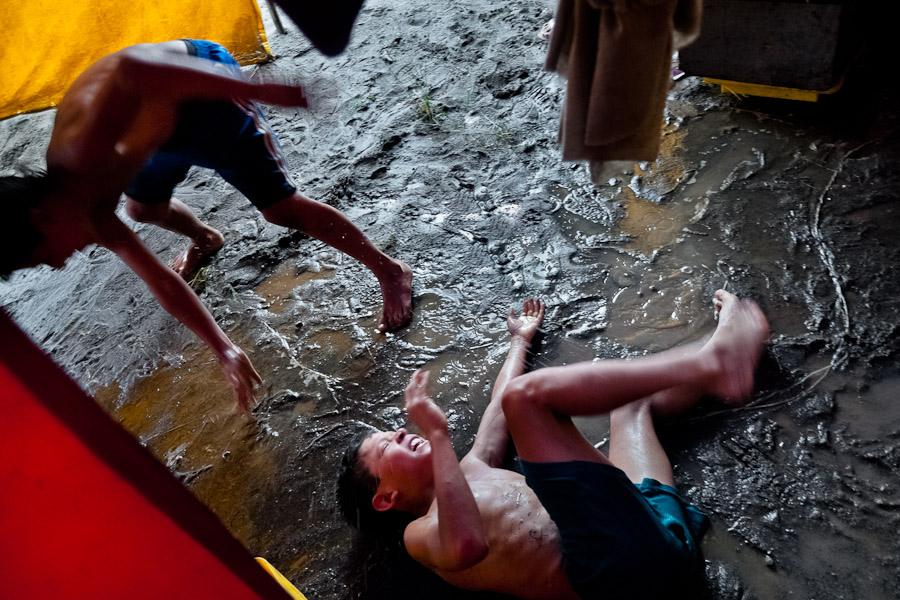 A Colombian boy falls into a mud during a friendly fight at the Circo Anny, a family run circus wandering the Amazon region of Ecuador.